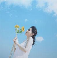 向日葵を持つ日本人の若い女性