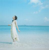 波打ち際で風を感じる日本人の若い女性