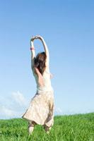 草原で伸びをする女性の後姿