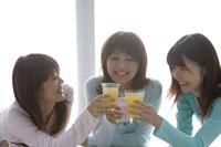 ジュースで乾杯する20代女性3人