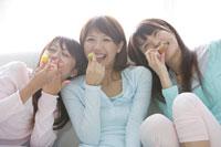 ソファでお菓子を食べる女性3人