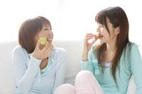 ソファでお菓子を食べる女性2人 30018000018B| 写真素材・ストックフォト・画像・イラスト素材|アマナイメージズ