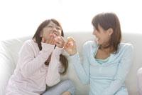 ソファでお菓子を食べる女性2人 30018000019A| 写真素材・ストックフォト・画像・イラスト素材|アマナイメージズ
