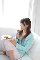 ソファでお菓子を食べる20代女性