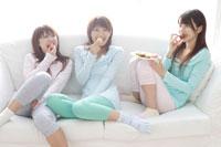 ソファでお菓子を食べる女性3人 30018000023C| 写真素材・ストックフォト・画像・イラスト素材|アマナイメージズ