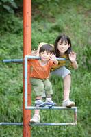 公園の遊具で遊ぶ弟と姉
