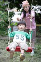 ブランコで遊ぶ姉と弟