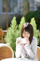 カフェでコーヒーを飲む20代女性