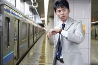 駅のホームで腕時計を見る男性