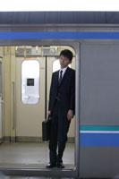 電車の開いたドアの傍に立つ男性