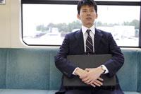 鞄を抱え電車の座席に座る男性