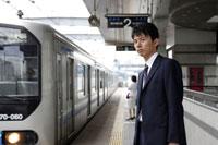 駅のホームで電車を待つ男性