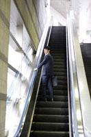 駅のエスカレーターを上る男性