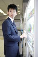 自動販売機のボタンを押す男性