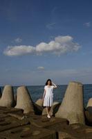 防波堤を歩く白い服の女性