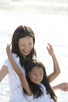 海辺の女性と抱っこされる女の子