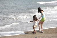 波打ち際の女性と女の子