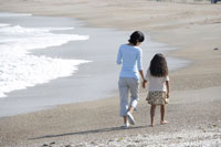 波打ち際を歩く親子