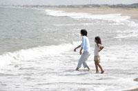 波打ち際で貝を投げる親子