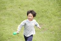 野原でバットを持って走る男の子