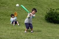 野原で野球をする双子の男の子