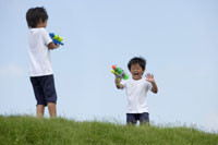 水鉄砲で遊ぶ双子の男の子