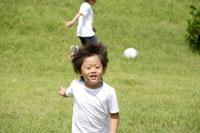 野原でサッカーをする男の子