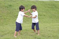 野原で遊ぶ双子の男の子