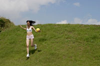 芝生を駆け下りる女性
