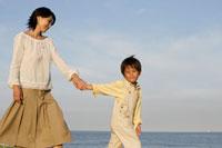 手を繋いで歩くお母さんと男の子