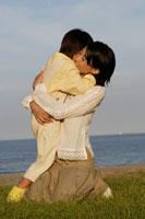 抱きしめ合う息子と母親