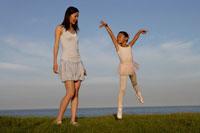 芝生でバレエを踊る女の子と女性