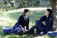 木陰で談笑する女子高生2人