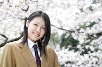 桜をバックにした制服姿の女子高生