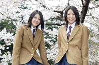 桜をバックにした制服姿の女子高生2人