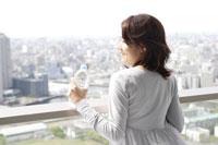 ベランダで水を飲む日本人女性