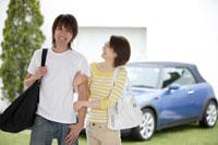 車の前に腕を組んで立つ日本人男女