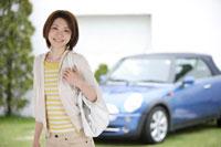 車の前に立つ日本人女性