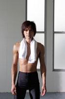 首にタオルをかけて佇む日本人男性