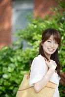 植木の前に立つ日本人女性