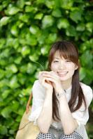 植木の前に座る日本人女性