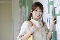 掲示板の前に立つ日本人の女子学生