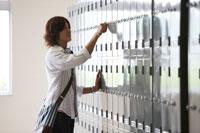 ロッカーの前に立つ日本人の男子学生 30018001123| 写真素材・ストックフォト・画像・イラスト素材|アマナイメージズ