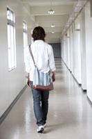 学校の廊下を歩く日本人の男子学生の後姿