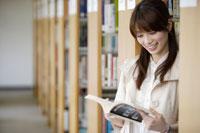 図書館で本を読む日本人の女子学生