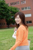 キャンパスの芝生を歩く日本人女性