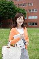 キャンパスの芝生に佇む日本人女性