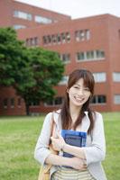 キャンパスで本を抱える日本人女性 30018001249A| 写真素材・ストックフォト・画像・イラスト素材|アマナイメージズ