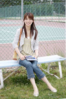 ベンチに座って本を読む日本人女性