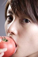 トマトをかじる20代日本人女性のビューティーイメージ